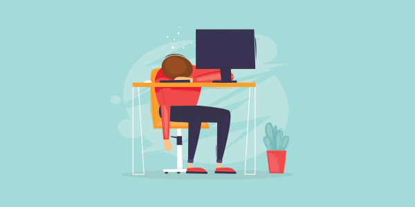 man-slumped-over-desk